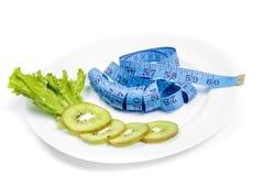 吃健康 测量的磁带和新鲜的猕猴桃 库存图片