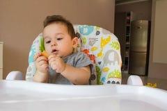 吃儿童饼干的画象逗人喜爱的男婴婴孩的第一食物10个月 学会小孩的男孩与牙固体foo居住 免版税图库摄影