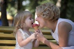 吃冰母亲的奶油色女儿 库存图片