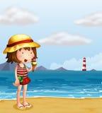 吃冰淇凌的一个女孩在海滨 库存图片