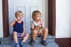吃冰淇凌的两个小兄弟姐妹男孩。 免版税库存照片