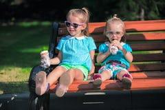 吃冰淇凌的两个小可爱的女孩 库存照片