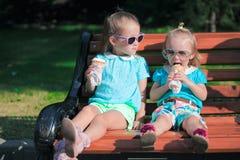 吃冰淇凌的两个小可爱的姐妹 库存照片