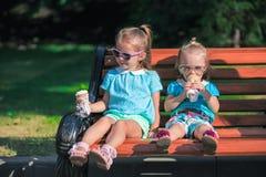 吃冰淇凌的两个小可爱的姐妹 免版税图库摄影