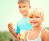 吃冰淇凌的两个愉快的孩子户外 免版税库存图片