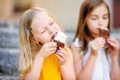 吃冰淇凌的两个逗人喜爱的妹,当坐台阶在夏日时 免版税库存照片