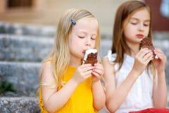 吃冰淇凌的两个逗人喜爱的妹,当坐台阶在夏日时 免版税库存图片