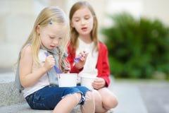 吃冰淇凌的两个逗人喜爱的妹,当坐台阶在夏日时 图库摄影