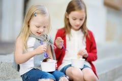 吃冰淇凌的两个逗人喜爱的妹,当坐台阶在夏日时 免版税图库摄影