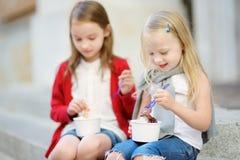吃冰淇凌的两个逗人喜爱的妹,当坐台阶在夏日时 库存图片