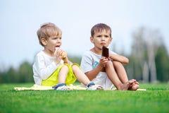 吃冰淇凌的两个年轻男孩 免版税库存图片