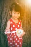 吃冰淇凌的亚裔女孩在夏日 户外 温暖 图库摄影
