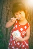 吃冰淇凌的亚裔女孩在夏日 户外 温暖 库存照片