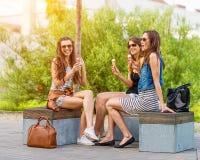 3吃冰淇凌的俏丽的妇女在镇里,坐长凳,笑 库存照片