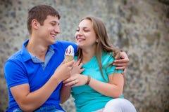 吃冰淇凌的夫妇在公园 免版税图库摄影