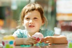 吃冰淇凌的女孩在室外咖啡馆 图库摄影