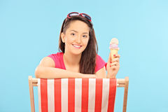 吃冰淇凌的妇女供以座位在太阳懒人 库存图片