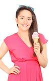 吃冰淇凌的妇女的垂直的射击 免版税库存照片