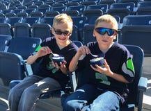吃冰淇凌的孩子在空的棒球公园 免版税库存图片