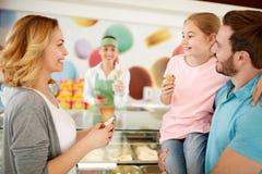 吃冰淇凌的家庭在面包店 库存图片