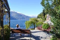 吃冰淇凌的少女坐长凳在湖科莫湖湖边平地在一个美好的晴朗的春日 库存照片