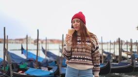吃冰淇凌的年轻女人在蓝色平底船的船夫附近 股票录像