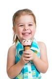 吃冰淇凌的愉快的儿童女孩在查出的工作室 免版税库存图片