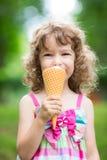 吃冰淇凌的愉快的孩子 免版税库存图片
