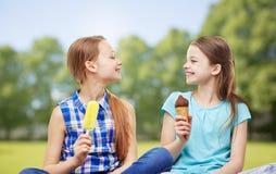 吃冰淇凌的愉快的小女孩在夏天公园 免版税库存图片
