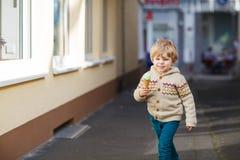 吃冰淇凌的愉快的小男孩,户外 免版税库存图片