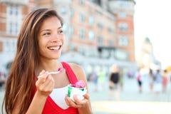 吃冰淇凌的愉快的旅游妇女在魁北克 免版税库存图片