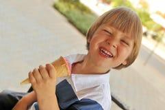 吃冰淇凌的愉快的男孩 库存照片