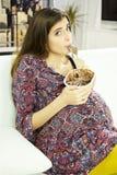 吃冰淇凌的愉快的美丽的孕妇做滑稽的面孔 库存图片