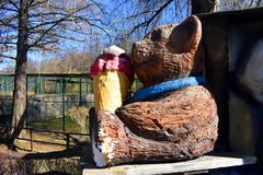 吃冰淇凌的木熊玩偶在公园 库存照片