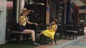 吃冰淇凌的母亲和女儿在街道咖啡馆在夏日 股票录像