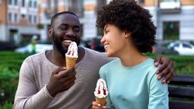 吃冰淇凌的约会夫妇,一起坐城市长凳,获得乐趣,爱 库存照片