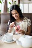 吃冰淇凌的美丽的深色的少妇特写镜头画象在有的餐馆乐趣愉快的微笑的图象 免版税库存图片