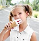 吃冰淇凌的逗人喜爱的微笑的小女孩 免版税库存照片