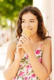 吃冰淇凌的年轻愉快的妇女画象  免版税库存图片