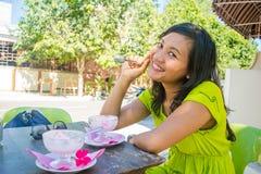 吃冰淇凌的年轻美丽的亚裔女孩画象在室外咖啡馆和微笑 库存照片
