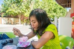 吃冰淇凌的年轻美丽的亚裔女孩画象在室外咖啡馆 图库摄影