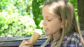 吃冰淇淋的孩子在操场,女孩放松的坐长凳在公园4K