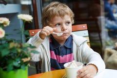 吃冰冻酸奶酪在咖啡馆的可爱的小男孩冰淇凌 免版税库存图片