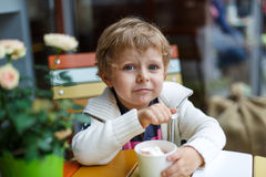 吃冰冻酸奶酪在咖啡馆的可爱的小男孩冰淇凌 库存图片