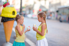吃冰creamin露天咖啡馆的愉快的小女孩 人们、孩子、朋友和友谊概念 免版税库存图片