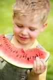 吃切片西瓜的孩子的画象 免版税库存照片
