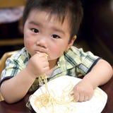 吃劫掠意大利面食的婴孩 免版税库存照片