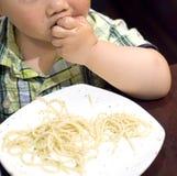 吃劫掠意大利面食的婴孩 库存照片