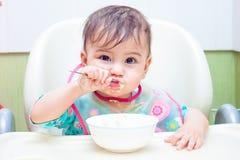 吃匙子的婴孩 免版税库存照片