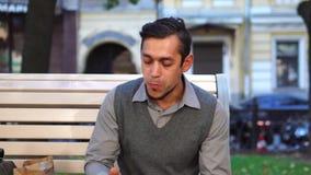 ?? 吃午餐和喝咖啡的一个年轻办公室工作者外部在城市 股票录像